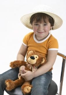 坐在椅子上抱着布娃娃的快乐孩子图片